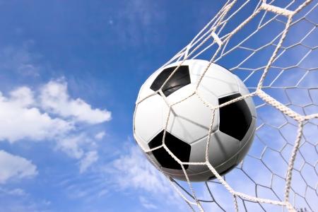close-up von einem Fußball (Fußball) gehen in die Rückseite des Netzes mit einem blauen Himmel im Hintergrund Lizenzfreie Bilder