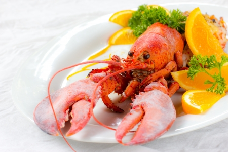 lobster dinner: Lobster Thermidor and orange on white background