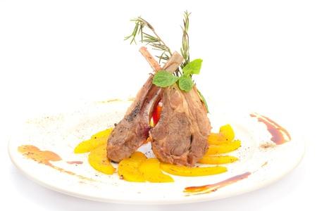Lammkarree mit gegrilltem Pfirsich auf weißem Teller
