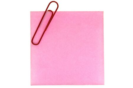 pink sheet of paper and red clip on a white background photo