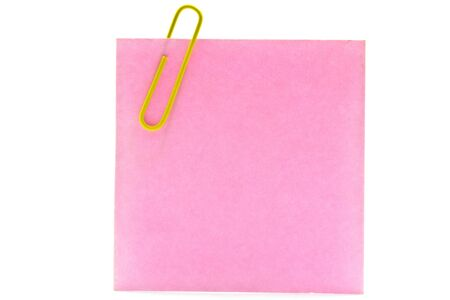 pink sheet of paper and yellow clip on a white background photo
