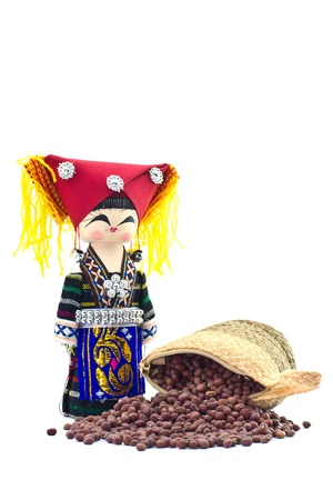 the souvenir dolls in hill tribe clothes and sack with red beans, azuki bean spilling out over on white background photo
