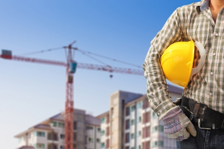 building site: Worker and the blurred construction background in blue sky