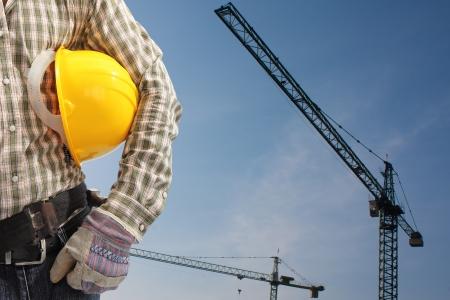 Builder Arbeiter in Uniform und Helm Betrieb mit Turmdrehkran