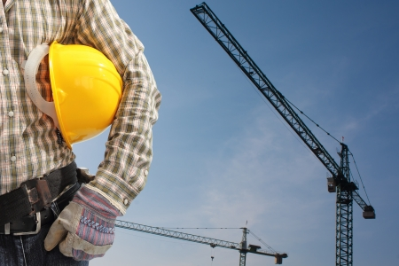 builder worker in uniform and helmet operating with tower crane photo