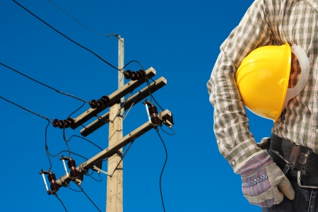 lineman: Electrician worker at work against electric post and blue sky background
