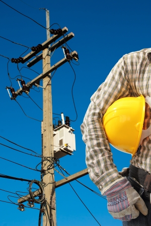 Electrician worker at work against electric post and blue sky background Stock Photo - 17149733