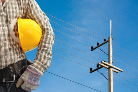 Electrician worker at work against electric post and blue sky background photo