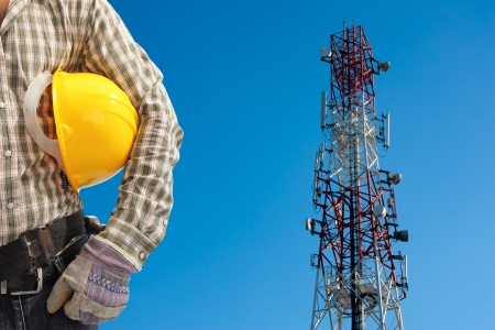 technician against telecommunication tower, painted white and red in a day of clear blue sky.  Standard-Bild