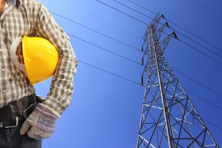 grid: Electrician and high voltage power pylon against blue sky  Stock Photo
