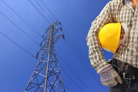 Electrician and high voltage power pylon against blue sky Standard-Bild