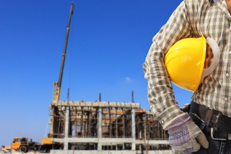 Worker and the blurred construction against blue sky