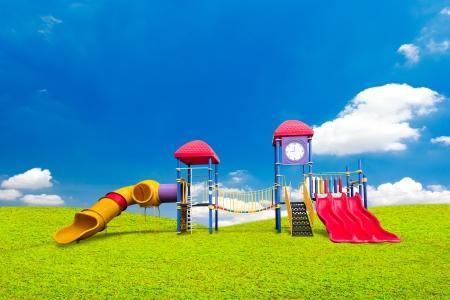 jardin de infantes: zona de juegos de colores en la hierba verde y el cielo azul de fondo Foto de archivo
