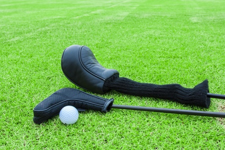 golf bags and golf ball on a tee in green grass course photo