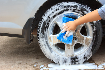 car service: cleaning the wheel car wash with a sponge Stock Photo