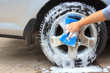 Reinigen Sie das Rad Autowäsche mit einem Schwamm