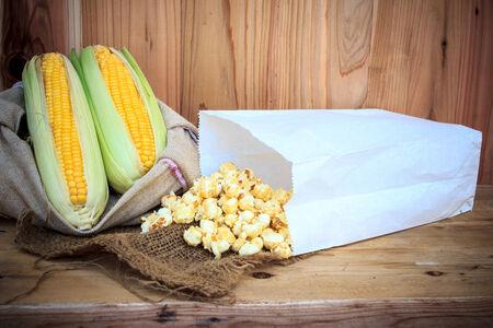 popped: fresh corn and popcorn bag on wood background