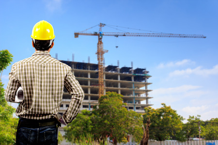 architect with holding blueprints looking at the blurred construction background in blue sky Standard-Bild