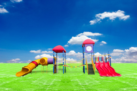 kinder garden: colorful playground on green grass against blue sky background