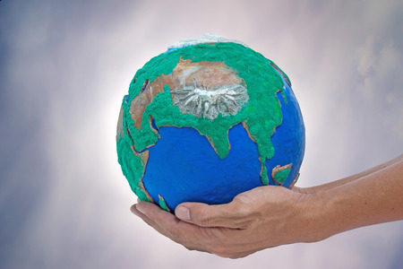 lurid: man his hands holding globe made from clay on gray lurid sky Stock Photo