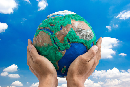 hands holding globe: man holding globe made from clay on his hands  with blue sky background