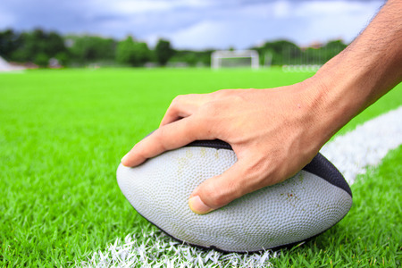 Rugby-Ball in der Hand auf grünem Gras Standard-Bild - 26426396