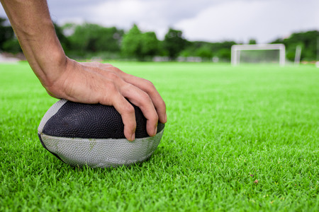 try: rugby ball in hand on green grass