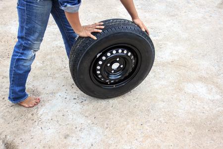 woman during changing car wheel at road photo