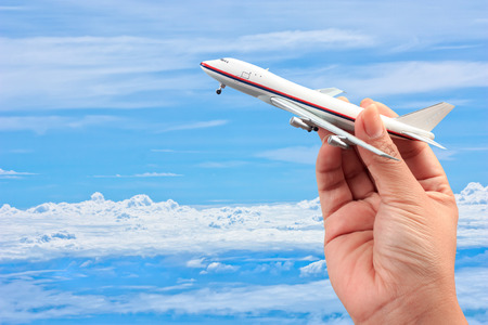 woman hand holding a model plane on blue sky and white cloud background Standard-Bild