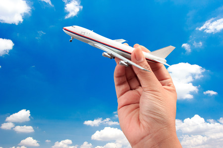 woman hand holding a model plane with blue sky background