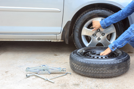 woman removing a wheel  car on the roadside