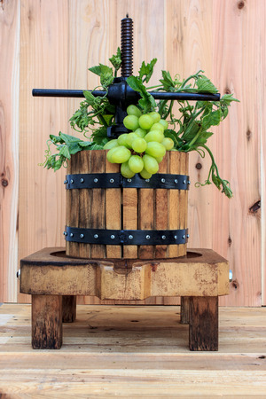 winepress: manual grape crushing machine on wood background Stock Photo