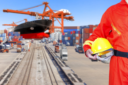 Dock worker holding hard hat for controlling work process container ship being unloaded with  in the harbor Standard-Bild