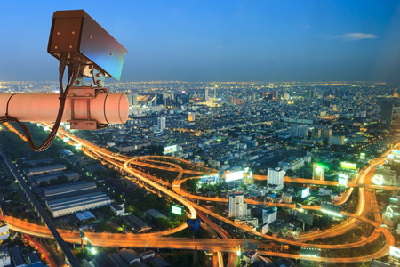 Security Camera or surveillance Operating on traffic road and urban on Skyscraper rooftop in sunset Standard-Bild