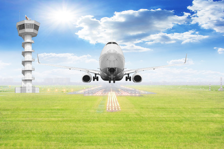 Passenger aircraft takeoff on runway with air traffic control tower of airport Standard-Bild