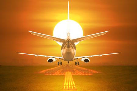 Rear view passenger aircraft takeoff on runway in sunset Standard-Bild