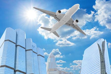 Passenger aircraft  flying above high building skyscrapers Standard-Bild