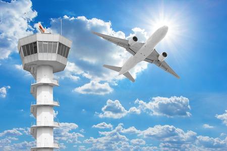 Passagiersvliegtuigen vliegen boven de luchtverkeersleiding toren tegen de blauwe hemel