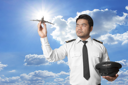 Pilot with model airplane against blue sky background