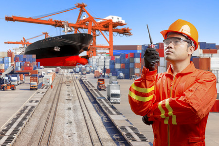 Dock worker with radio communication for controlling work process commercial ship loading container in shipping port transport and industry logistic in the harbor
