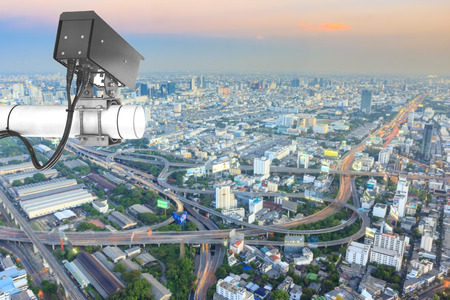 Security Camera or surveillance Operating on traffic road and urban on Skyscraper rooftop in sunrise