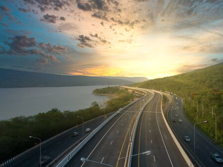 Aerial view of highway on passing through the lush greenery tropical rainforest mountain in sunrise scenery
