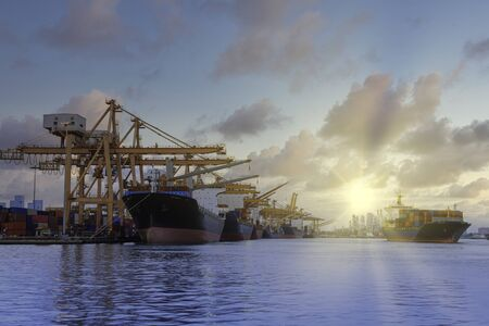 Container cargo freight ship with crane bridge in shipyard in sunrise for logistic Import and export. Industrial and transportation concept