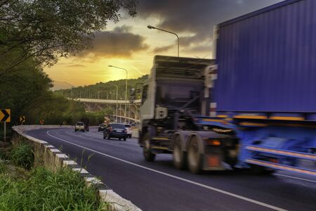 Motion blur of container truck on the countryside road with mountain against sunset