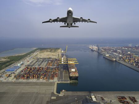 Aerial view of airplane flying above modern ship cargo containers entering to harbor with export and import business and logistics, world wide cargo transportation concept. Standard-Bild