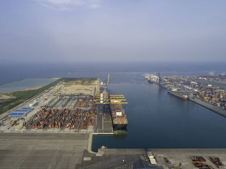 Aerial view of modern ship cargo containers entering to harbor with export and import business and logistics.