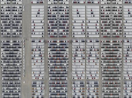 Aerial view of new cars from the manufactory parked at the port for import export business logistic and transportation by large transport ship