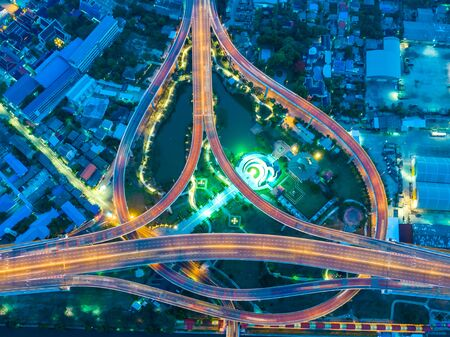 Aerial view of night vision above the road traffic highway interchange overpass turn arounds and transportation in city