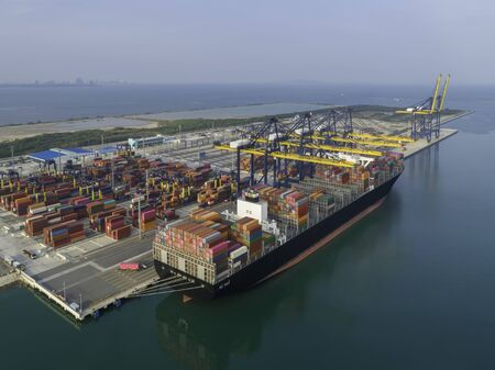 Aerial view of ship cargo containers entering to modern harbor with export and import business and logistics, world wide cargo transportation concept. Standard-Bild