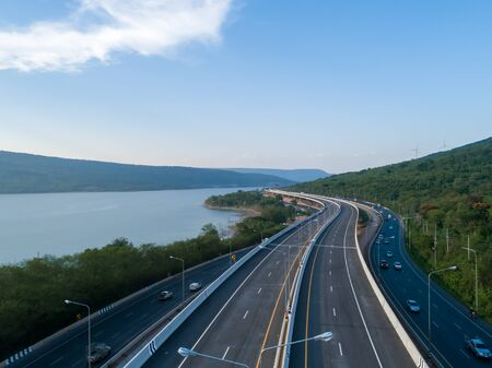 Arial view of highway on passing through the lush greenery tropical rain forest mountain that connected in sunrise scenery